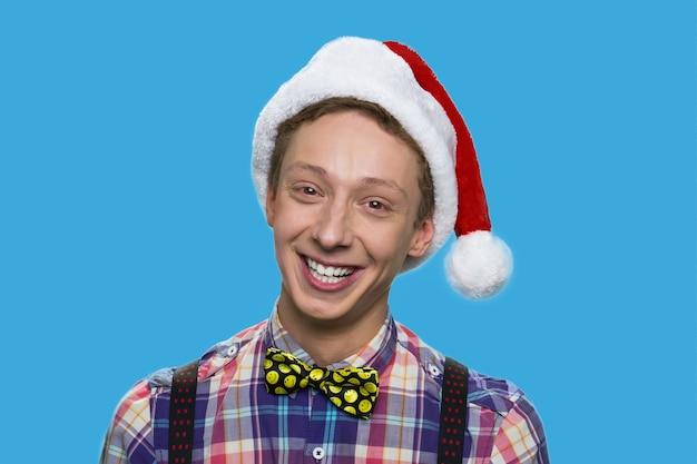 Vrolijke schooljongen in kerstmuts. lachende tiener met bowtie geïsoleerd op blauwe achtergrond.