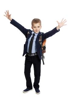 Vrolijke schooljongen in uniform met een rugzak met zijn handen omhoog.
