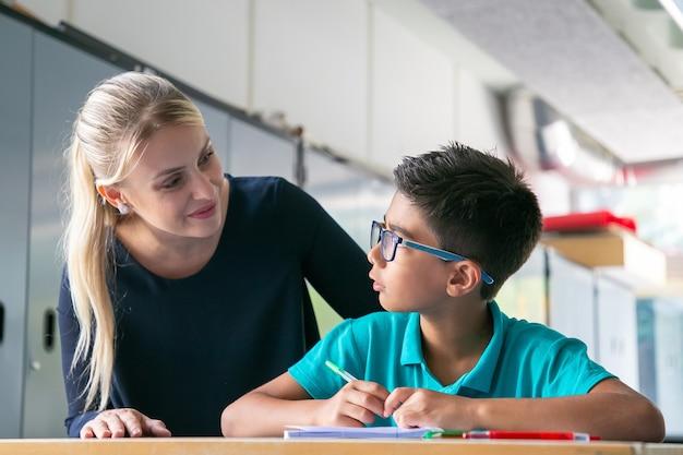 Vrolijke schoolleraar die schooljongen in de klas helpt en ondersteunt