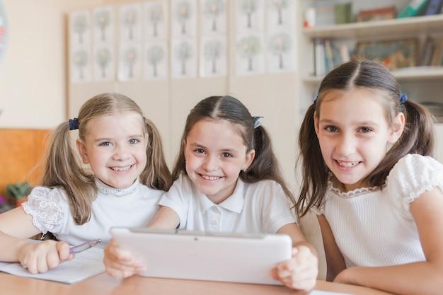 Vrolijke schoolmeisjes met tablet camera kijken