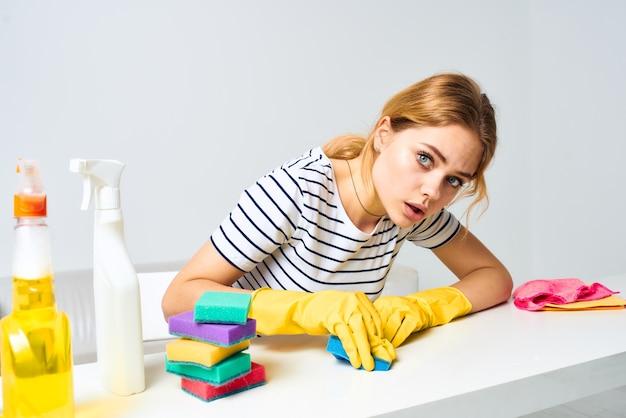 Vrolijke schoonmaakster veegt de tafel af met schoonmaakmiddelen