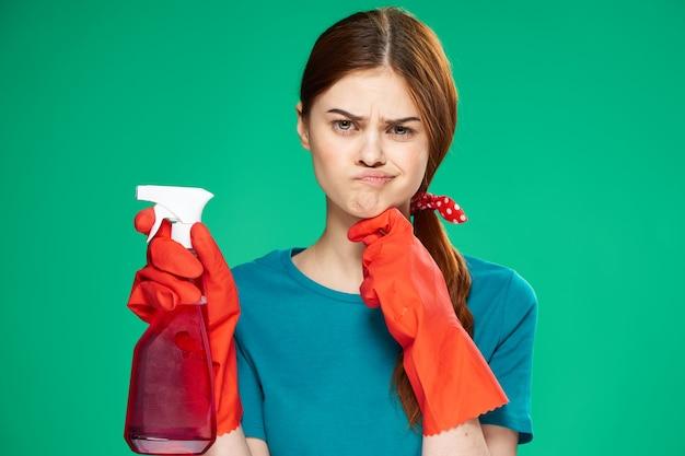 Vrolijke schoonmaakster wasmiddelen rubberen handschoenen thuiszorg groene achtergrond