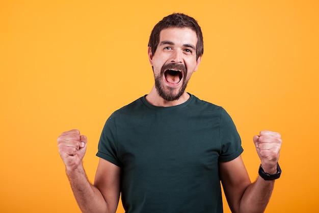Vrolijke schreeuwende opgewonden man met zijn mond open van emoties op oranjegele achtergrond. portret van expressie en geluk