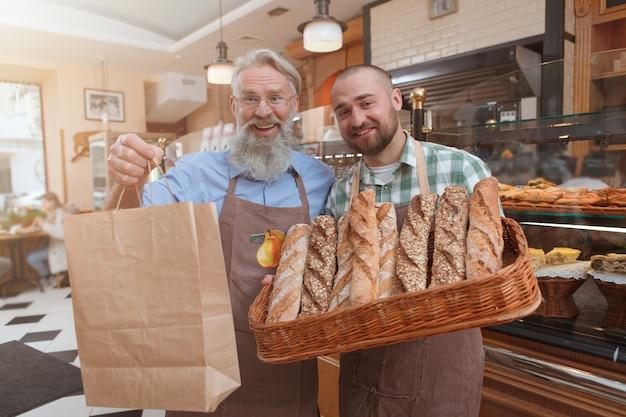 Vrolijke senior bakker knuffelen zijn zoon met papieren boodschappentas met heerlijk vers brood