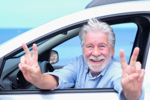 Vrolijke senior bebaarde man in zijn auto maakt een positief gebaar met handen. optimistische ouderen genieten van pensioen en vrijheid. horizon over water