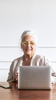 Vrolijke senior ceo met behulp van een laptop