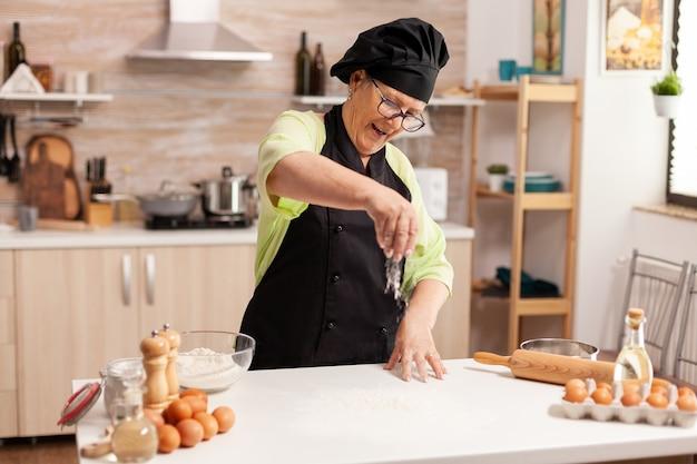 Vrolijke senior dame die pizza maakt in de keuken van het huis met behulp van topmeel voor het bakken. gelukkige bejaarde chef-kok met uniform besprenkelen, zeven met de hand zeven van ruwe ingrediënten.