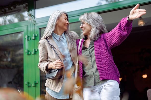 Vrolijke senior dame met bril laat iets zien aan grijsharige aziatische vriend op straat in de stad