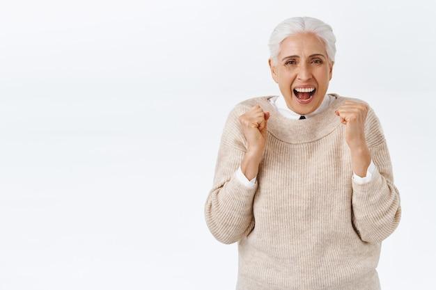 Vrolijke senior gelukkige vrouw met grijs haar in elegante outfit, oude leraar kreeg eindelijk pensioen, juichende vuistpomp, balde armen en dansen als vieren, gelukkig glimlachen, triomferen winnen prijs