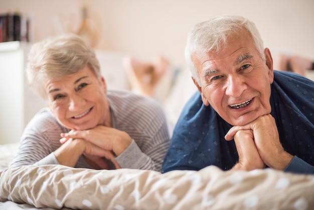 Vrolijke senior huwelijk rusten in de slaapkamer