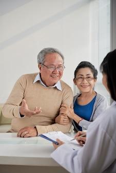 Vrolijke senior man en vrouw praten met vastgoedmanager en vertellen haar hun voorkeuren en e...