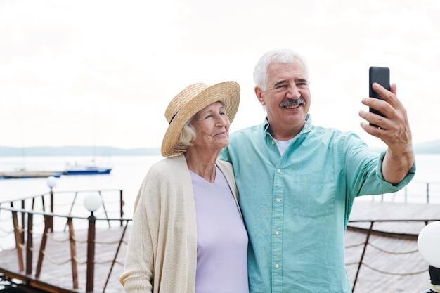 Vrolijke senior man en vrouw selfie met smartphone maken op zomerdag
