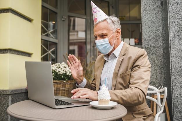 Vrolijke senior man viert verjaardag met videocall op café terras
