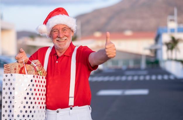 Vrolijke senior man winkelen voor kerstmis in een kerstmuts met een boodschappentas vol geschenken