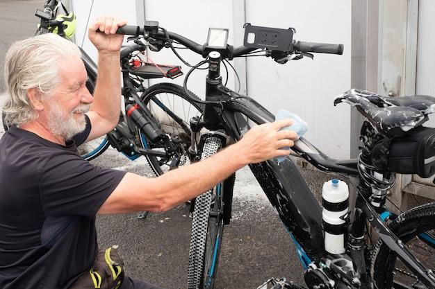 Vrolijke senior man witte baard en haar wast zijn fiets en zorgt voor de details. servicestation. hogedrukpomp