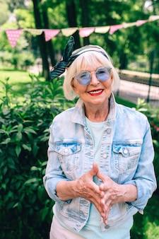 Vrolijke senior oude stijlvolle vrouw met grijs haar en in blauwe bril en denim vakantiemaster