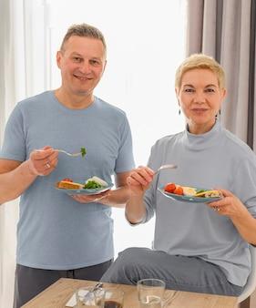 Vrolijke senior paar samen eten gezond ontbijt gelukkig leven van gepensioneerden