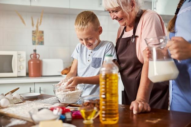 Vrolijke senior vrouw die gelukkig kookt met twee kleinkinderen