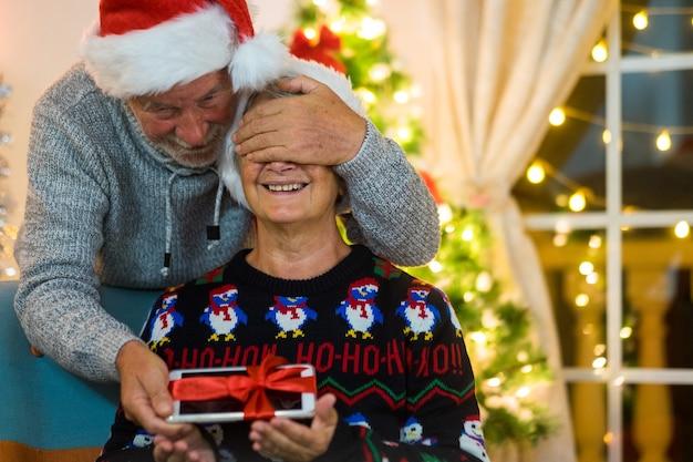 Vrolijke senior vrouw die lacht terwijl ze een kerstcadeau ontvangt. het dragen van hoeden van de kerstman vieren kerstvakantie. liefde en sereniteit concept