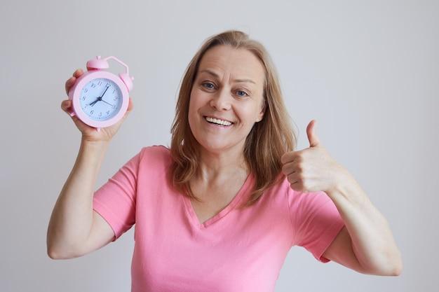 Vrolijke senior vrouw in een roze shirt, houdt een wekker, toont een duim. foto op een grijze achtergrond.