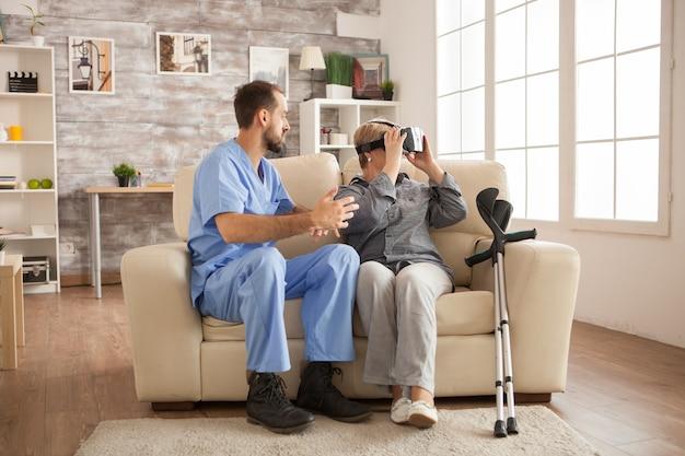Vrolijke senior vrouw in verpleeghuis met behulp van vr-headset.