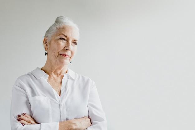 Vrolijke senior vrouw met gekruiste armen bij het raam in een witte kamer in een witte kamer