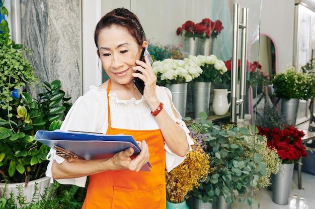 Vrolijke senior vrouwelijke bloemist praten over de telefoon en bloemen en inpakpapier bestellen