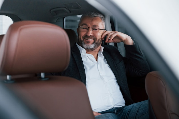 Vrolijke senior zakenman in brillen zittend op de achterkant van de auto en lachend