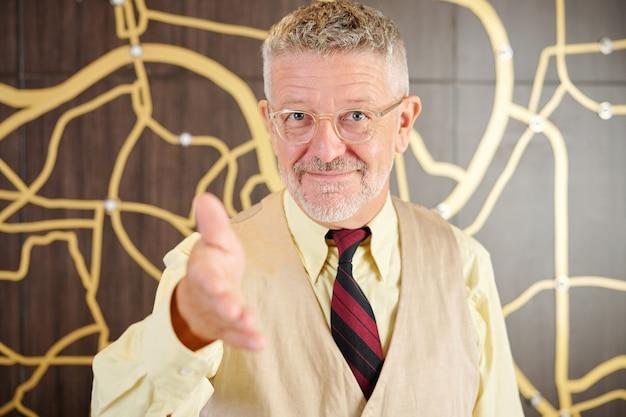 Vrolijke senior zakenman in glazen hand voor handdruk en groet partner