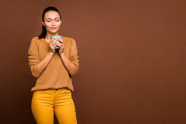 Vrolijke serene kalm lief mooi meisje genieten van ruikende koffie in beker houdt ze met handen met gesloten ogen geïsoleerd