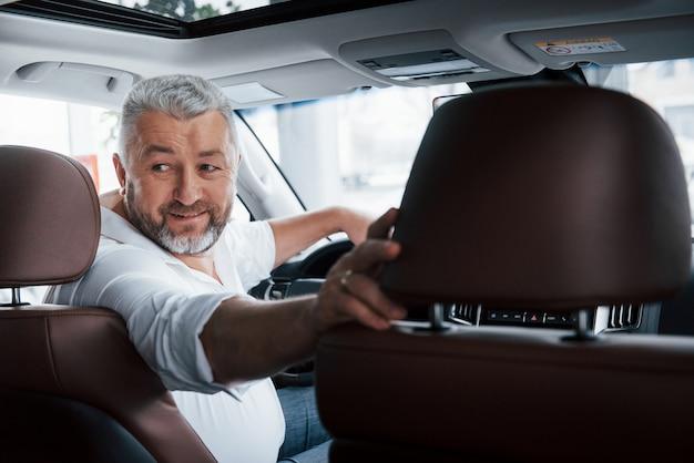 Vrolijke sfeer. rijden in een achteruitversnelling. achterom kijken. man in zijn gloednieuwe auto