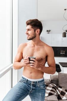 Vrolijke shirtless jongeman permanent in de buurt van het raam en koffie drinken in de keuken