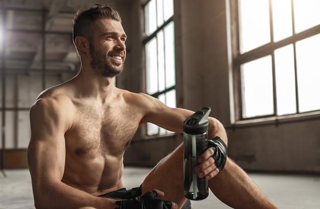 Vrolijke shirtless sportman met fles water glimlachend en wegkijken zittend op de vloer tijdens pauze in fitnesstraining in de sportschool