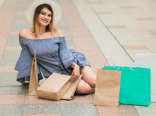 Vrolijke shopaholic vrouw in hoed en jurk zittend op de vloer met papieren boodschappentassen