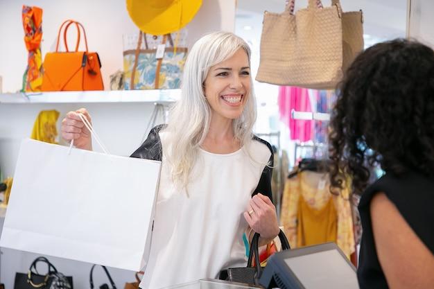 Vrolijke shopper met papieren zakken en glimlachend bij kassier of verkoper in mode winkel. vrouw die aankoop neemt en winkel verlaat. gemiddeld schot. winkelen concept
