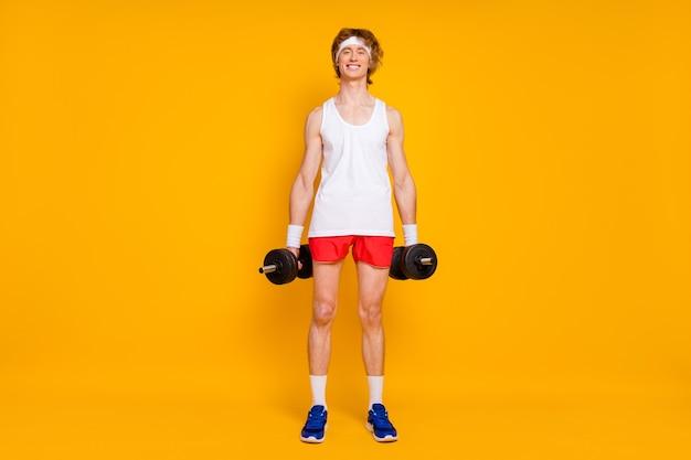 Vrolijke slanke jongenssportman die barbell uitwerkt