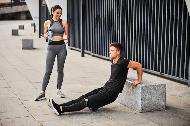 Vrolijke slanke vrouw drinkt water terwijl ze naar een atletische man kijkt die triceps push-ups doet