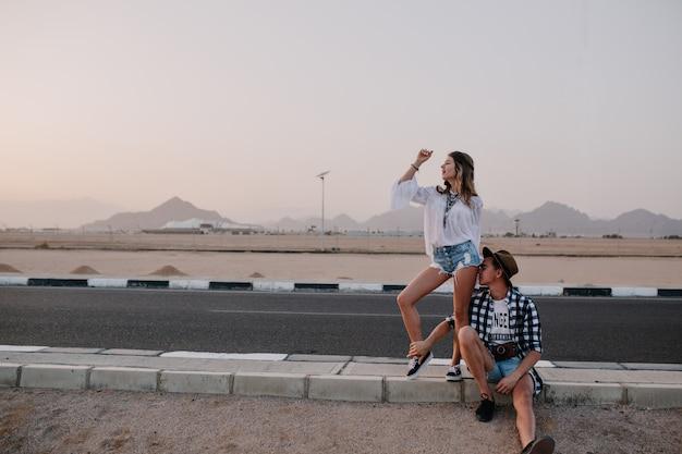 Vrolijke slanke vrouw grappig dansen terwijl haar vermoeide vriendje rusten op de weg op de berg. portret van schattige jonge vrouw en man reizen door land en wachten op een ritje op de snelweg