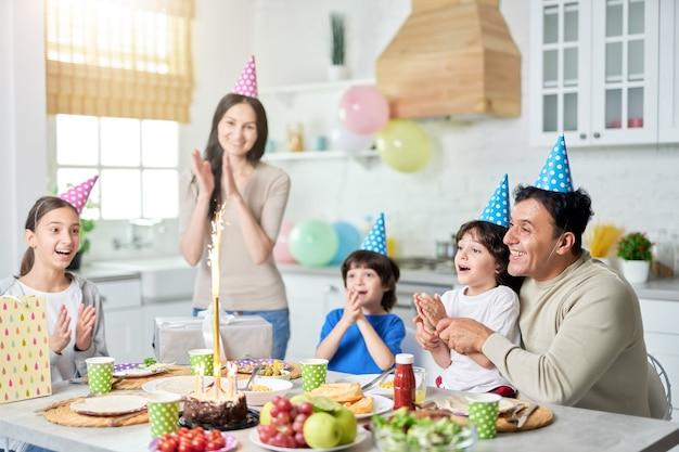 Vrolijke spaanse familie met kinderen die er gelukkig uitzien, klappen terwijl ze thuis samen verjaardag vieren. ouderschap, vieringsconcept. selectieve focus