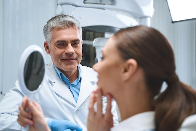 Vrolijke specialist kijkt naar vrouw terwijl ze in de spiegel kijkt na tandheelkundige ingrepen