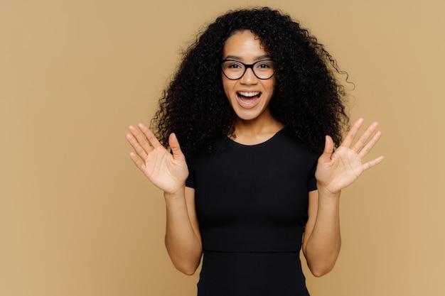 Vrolijke speelse afro-amerikaanse vrouw steekt handpalmen op, voelt zich opgewonden, drukt geluk uit