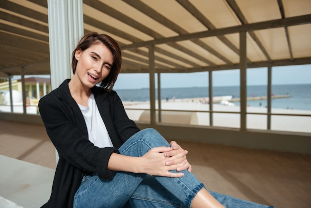 Vrolijke speelse jonge vrouw zitten en knipogen in prieel aan de kust