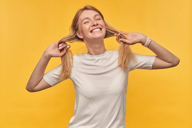 Vrolijke speelse vrouw met sproeten in witte t-shirt met haar als paardenstaarten en lachend op geel