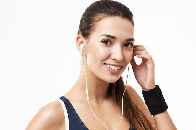 Vrolijke sportieve geschiktheidsvrouw die in oortelefoons op wit glimlacht.