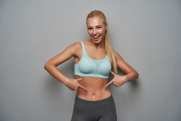 Vrolijke sportieve jonge blonde vrouw met casual kapsel trots wijzend op haar kubussen pers, gelukkig kijkend naar de camera en breed glimlachend, poseren over lichtgrijze achtergrond
