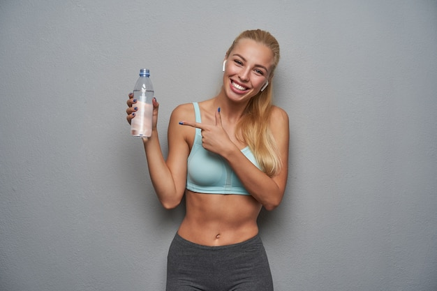 Vrolijke sportieve jonge blonde vrouw met lang haar fles water in de hand houden en erop wijzen met wijsvinger, vreugdevol kijkend naar camera met brede glimlach, geïsoleerd op lichtgrijze achtergrond
