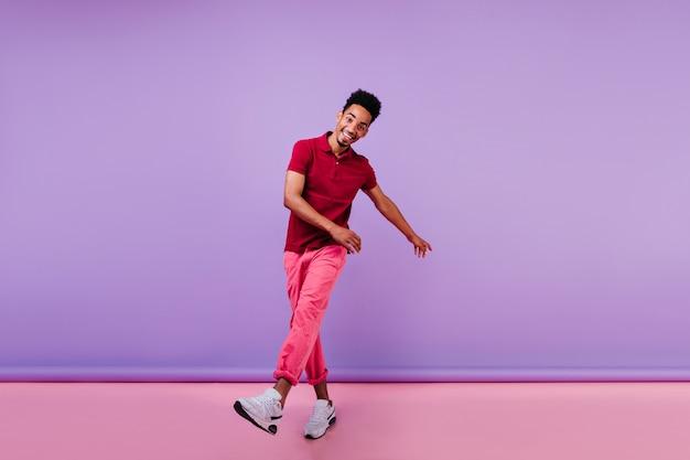 Vrolijke sportieve kerel in roze broek die geluk uitdrukt. emotionele zwarte jongeman dansen.
