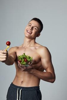 Vrolijke sportieve kerel plaat salade training energie gezond voedsel.