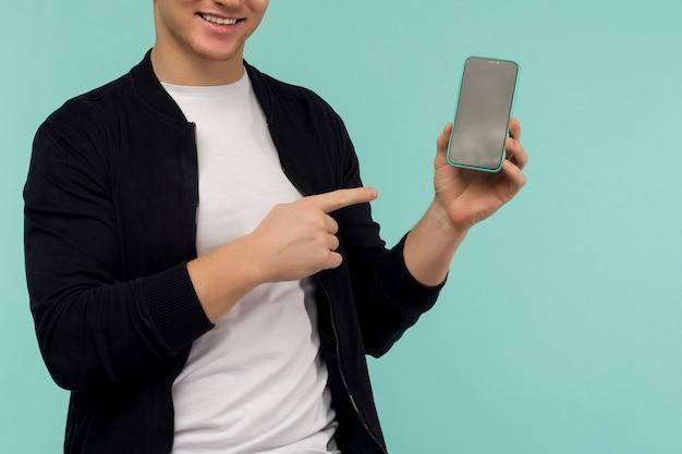 Vrolijke sportieve roodharige man toont een vinger op het scherm van de smartphone op een blauwe achtergrond. - afbeelding