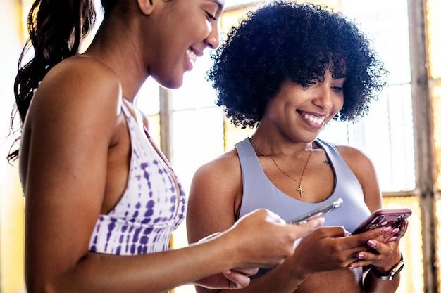 Vrolijke sportieve vrouwen die hun telefoon checken
